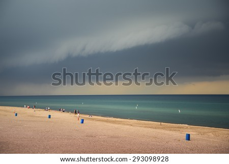 Storm clouds over lake Michigan beach - stock photo