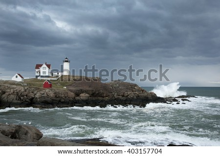 Storm clouds over Nubble lighthouse as waves crash on rocky coast in Maine. - stock photo