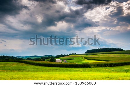 Storm clouds over rolling hills and farm fields in Southern York County, Pennsylvania. - stock photo