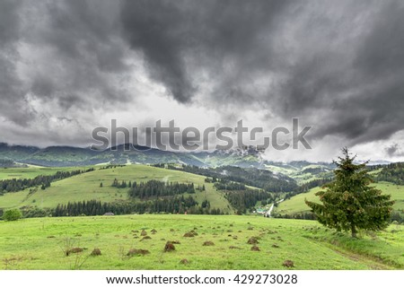 Storm clouds over the mountains and green meadows. - stock photo