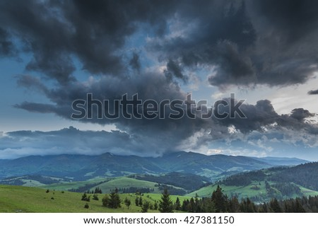 Storm clouds over the mountains and green meadows during sunset