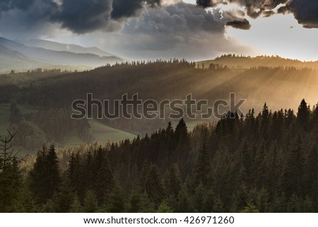 Storm clouds over the mountains and the forest during sunset. - stock photo