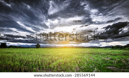 Storm Clouds panorama view before rainy and field meadow - stock photo
