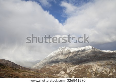 Storm clouds part to reveal sun on mountain peaks in high elevation British Columbia in fall. - stock photo