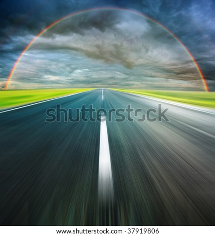 Storm clouds with rainbow above asphalt road - stock photo