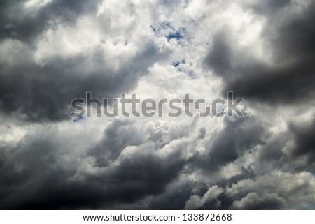Storm Clouds With Small Patches Of Blue Sky - stock photo