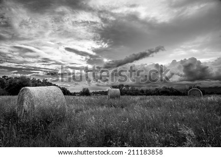 storm is coming on a field with hay bales