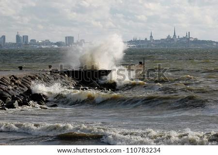 Storm on sea. Estonian capital Tallinn at background - stock photo