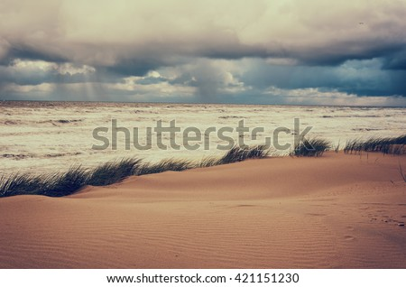 Storm over an ocean and sand dune, natural vintage hipster Instagram background - stock photo
