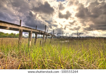 storm rising up over marsh with old dock - stock photo