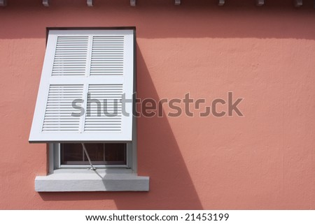 Storm shutter on pink wall of caribbean bungalow - stock photo