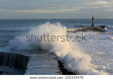 Storm waves over a pier and lighthouse from the north of Portugal - stock photo