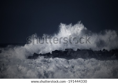 Storm waves over a pier in the north of Portugal. Black and white toned blue. - stock photo
