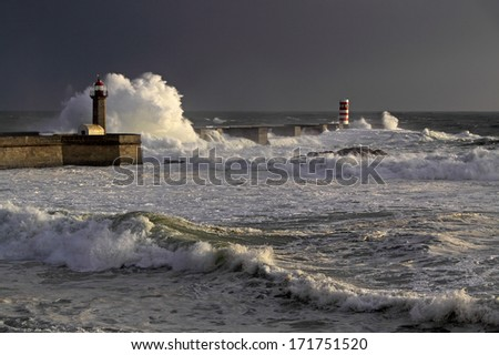 Storm waves over beacon and lighthouse of the harbor of river Douro, Portugal. Late evening light. - stock photo