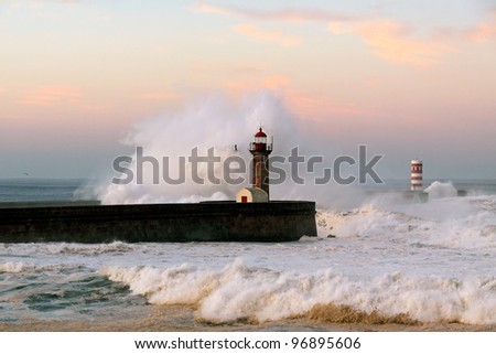 Storm waves over beacon of the harbor and lighthouse of river Douro, Portugal. Early morning light. - stock photo