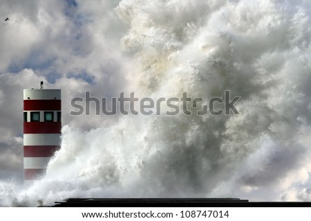 Storm waves over beacon of the harbor of Douro, Portugal - enhanced sky - stock photo