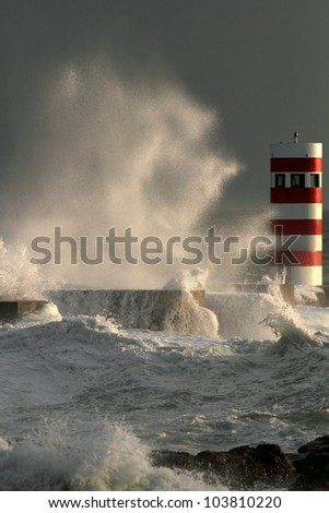 Storm waves over beacon of the harbor of river Douro, Portugal - stock photo