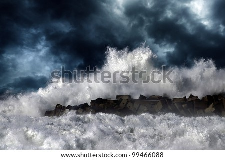 Storm waves over pier of the harbor of Povoa do Varzim, Portugal - enhanced sky - stock photo
