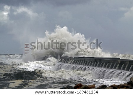 Stormy Atlantic waves against pier and beacon of the river Douro harbor entry, Porto, Portugal - stock photo