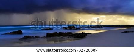 Stormy beach sunrise - stock photo