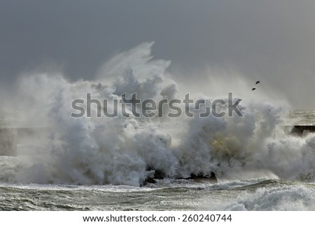 Stormy big waves against a pier from the north portuguese coast - stock photo