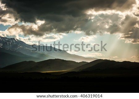 Stormy clouds in a blue sky over the mountains - stock photo