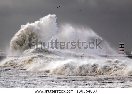 Stormy morning at the harbor of the mouth of the river Douro, in Porto, Portugal, with big waves against pier and beacon