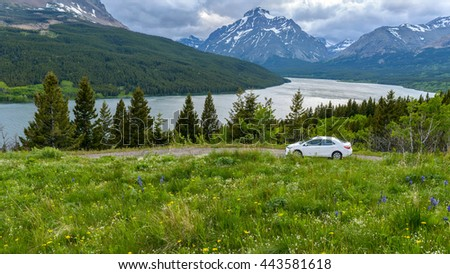 Stormy Mountain Lake Valley - A panoramic spring view of a stormy  evening at Lower Two Medicine Lake, with Rising Wolf Mountain in the background, Glacier National Park, Montana, USA. - stock photo