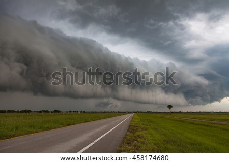 Stormy road ahead with large thunderstorm shelf cloud.