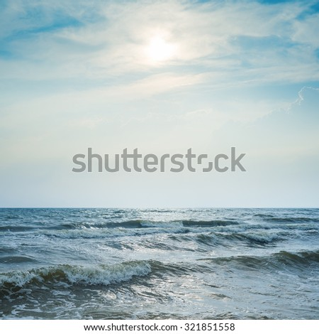 stormy sea and dramatic sky with sun - stock photo