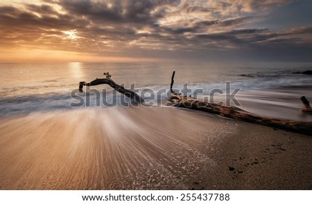 Stormy sea beach with slow shutter and waves flowing out - stock photo