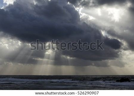 Stormy sea sky with dark clouds and sunbeams. Northern portuguese coast in November.