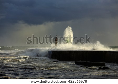 Stormy sea waves over pier and lighthouse with beautiful light before rain. Ave river mouth, Vila do Conde, north of Portugal.