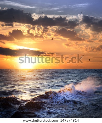 Stormy sea with sundown, clouds and birds / beautiful weather - stock photo