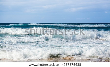 Stormy seas coming to the beach in parallel rows off Polihale Beach, Kauai, Hawaii - stock photo