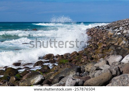 Stormy seas coming to the rocky breakwater and beach off Polihale Beach, Kauai, Hawaii - stock photo