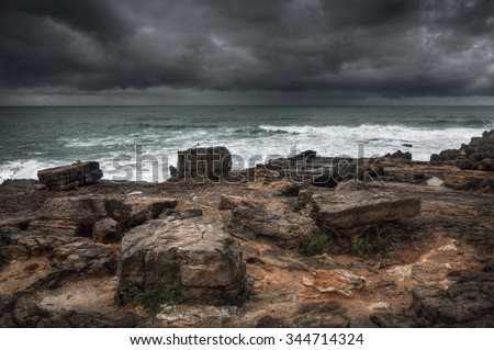 Stormy seascape with rocks in the foreground and dramatic cloudy sky - stock photo