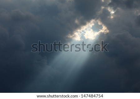stormy sky with a dramatic sunbeam - stock photo