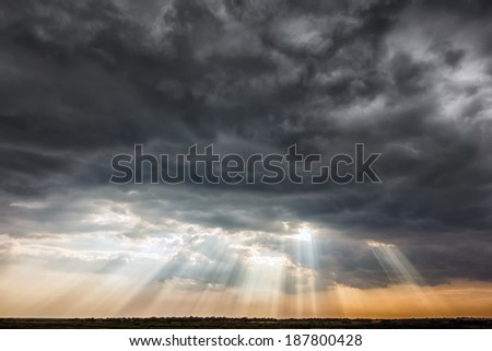Stormy sky with a dramatic sunrays between the clouds on spring evening in Greece  - stock photo