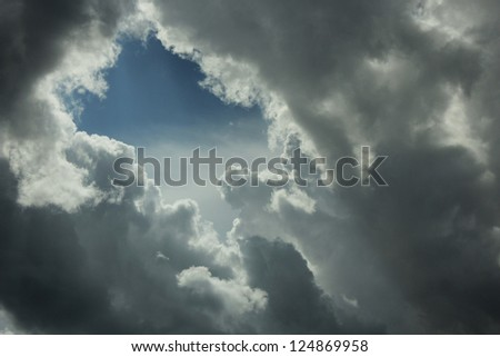 Stormy sky with opening showing a bright blue sky. - stock photo
