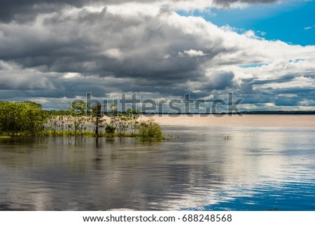 stormy skys and mixed sunshine at the confluence of the amazon river and the rio maranon