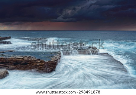 Stormy sunrise skies and turbulent seas at Maroubra - stock photo