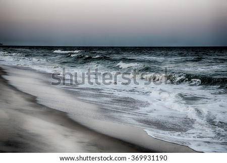 Stormy surf breaks on the beach at Kure Beach North Carolina. - stock photo