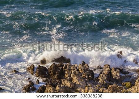 Stormy turbulent sea, waves hitting rocks at the coast. - stock photo