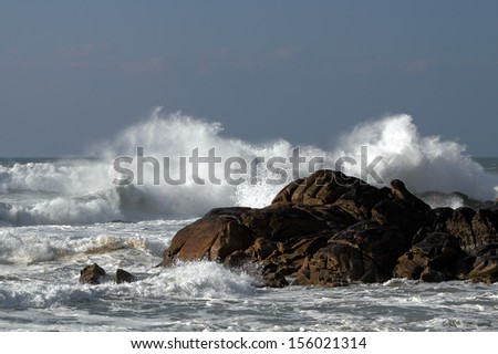 Stormy waves crushing on a rocky beach - stock photo