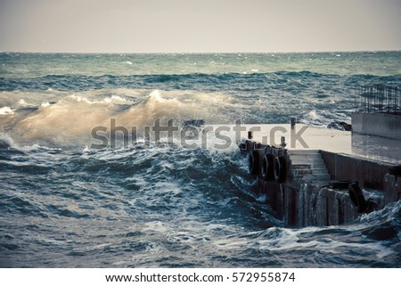 stormy waves of the sea crashing on the breakwater