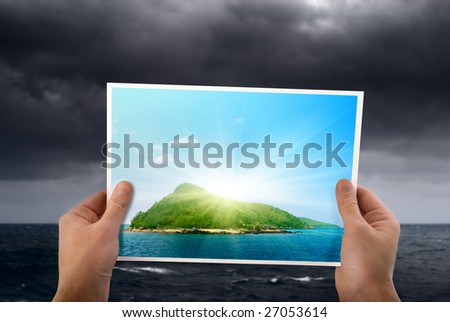 stormy weather and photo of tropical island in hands - stock photo