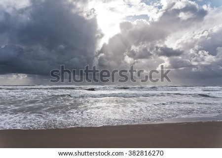 Stormy weather at sandy beach with sunrise - stock photo