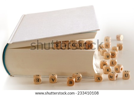 story - message for creative writing spelled with wooden letter blocks between pages of a white book, several blurry letter blocks around - stock photo
