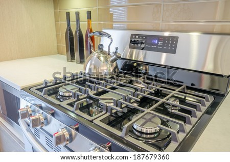 Stove closeup in modern kitchen interior with stainless steel gas cook-top - stock photo